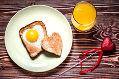 On the plate is toast with fried eggs inside a heart. Next on the plate is a little toast in the form of a heart. Royalty Free Stock Photos