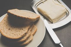 Plate with toasts and butter on dark table stock images