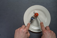 Plate with a Tomate cutten by cuttlery. Held by two hands Stock Image