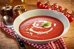 Plate of tomato cream soup. With greens, served on red checked napkin on wooden table. Different kinds of tomatoes and jar of oil in background stock image