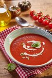 Plate of tomato cream soup. Rustic kitchen. White plate of red tomato cream soup with white sauce and herbs, served on checked napkin. Rustic kitchen concept stock photos