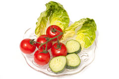 Plate with toms, cucumbers & lettuce. Tomatoes lettuce with cucumber on glass plate Royalty Free Stock Photography