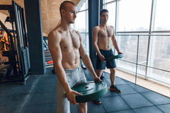 Plate training core group at gym fitness workout. Two men doing fitness exerciise at gym Royalty Free Stock Photography