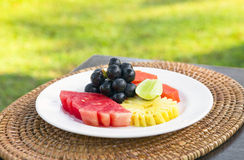 Plate with tropical fruits on the table stock photo