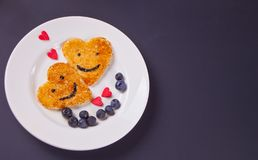 Plate of two pancakes in the shape of heart with berries on black table stock images