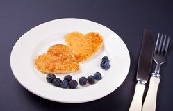 Plate of two pancakes in the shape of heart with berries on black table royalty free stock image