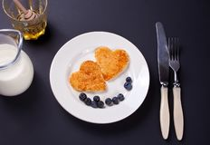 Plate of two pancakes in the shape of heart with berries on black table royalty free stock photos