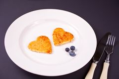 Plate of two pancakes in the shape of heart with berries on black table stock image