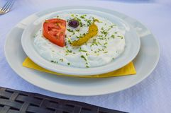 Plate of tzatziki with a tomato and an olive in a restaurant of Stock Photography