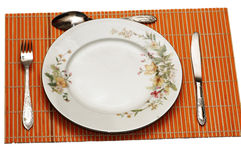 Plate and utensils. Served  on the orange mat Royalty Free Stock Photography