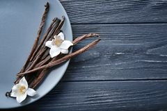 Plate with vanilla sticks and flowers. On wooden background Stock Photography