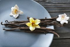 Plate with vanilla sticks and flowers. On wooden background Royalty Free Stock Photo