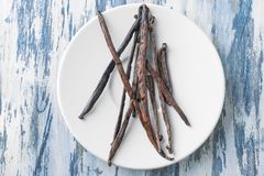 Plate with vanilla sticks. On wooden background Stock Photo