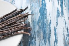 Plate with vanilla sticks. On wooden background Royalty Free Stock Photography
