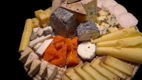 Plate of a variety of appetizing French cheeses. On a black background stock video footage