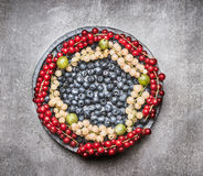 Plate with various colorful berries on gray stone background, top view Royalty Free Stock Photo