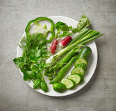 Plate of various fresh raw herbs and vegetables. On gray kitchen table, top view Royalty Free Stock Image