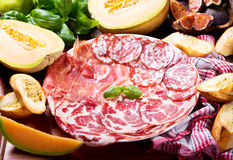 Plate of various ham and salami with fresh fruits Royalty Free Stock Photography