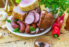 Plate various kinds sausages surrounded greens Royalty Free Stock Photos