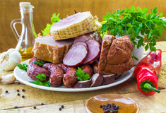 Plate various kinds sausages surrounded greens Royalty Free Stock Images