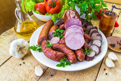 Plate various kinds sausages surrounded greens Stock Images
