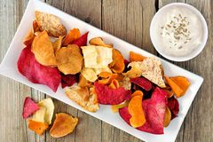 Plate of vegetable chips with dip from above on wood Royalty Free Stock Photos