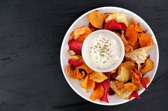 Plate of vegetable chips with dip, overhead view on slate Stock Photos