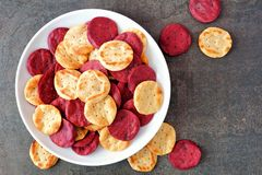 Plate of vegetable crisps, overhead view on slate. Plate of colorful organic vegetable crisps, overhead view on a slate background Royalty Free Stock Photography