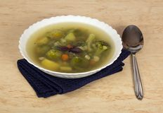 Plate of vegetable soup, spoon and blue napkin Stock Photography