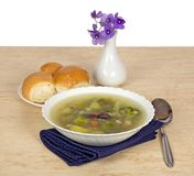 Plate of vegetable soup and violets Stock Photo
