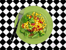 Plate of vegetables with fork on tablecloth Royalty Free Stock Photo