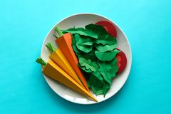 Plate with vegetables made from paper: carrots, tomato, spinach and arugula on blue background. Minimal, creative, vegan, healthy. Or food art concept. Copy stock images