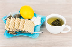 Plate with wafers and tea bags, sugar, lemon and teacup Royalty Free Stock Photography