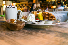 A plate of waffle with banana and strawberry, whipping cream, blueberry and syrup, delicious, yummy Royalty Free Stock Images