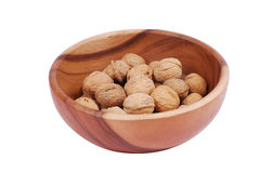 Plate with walnuts. Wooden plate with walnuts on a while background Royalty Free Stock Photos