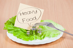 Plate with weight. Concept of heavy food. Plate with fork and weight on the table. Concept of heavy food Royalty Free Stock Photos