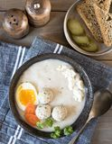 A plate with white Polish soup. White borsch with egg, meatballs, cottage cheese and carrots royalty free stock photo