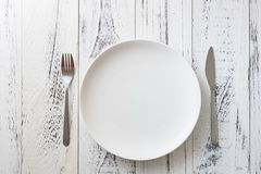 Plate on white wooden background with utensils Royalty Free Stock Photography