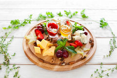 Plate with wine snacks in herbal frame on white Royalty Free Stock Photo