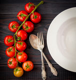 Plate on a wooden table with bunch tomatoes. Top view Royalty Free Stock Photos