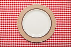 Plate on wooden table with red checked tablecloth Royalty Free Stock Photography