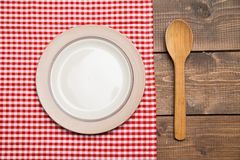 Plate on wooden table with red checked tablecloth Royalty Free Stock Photo