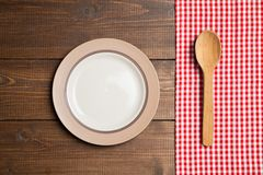 Plate on wooden table with red checked tablecloth Stock Photos