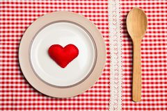 Plate on wooden table with red checked tablecloth Royalty Free Stock Image