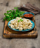 A plate wuth boiled ravioli on the wooden board. Front view of ravioli with the red sauce and a fork on the serviette, close up Stock Images