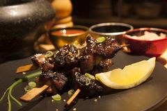 Japanese yakitori sticks. Plate with yakitori and sauces in a kitchen Royalty Free Stock Photo
