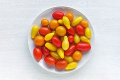 Plate with yellow and red tomatoes stock images