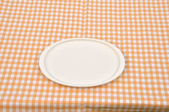 Plate on a yellow-white tablecloth Royalty Free Stock Photo
