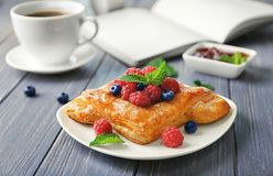 Plate with yummy berry puff pastry on table. Plate with yummy berry puff pastry on wooden table Stock Photography