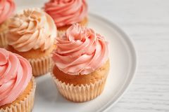 Plate with yummy cupcakes. On wooden table Stock Images